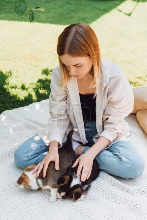 Photo for Blonde girl sitting on blanket in garden with cute puppies at sunny day - Royalty Free Image