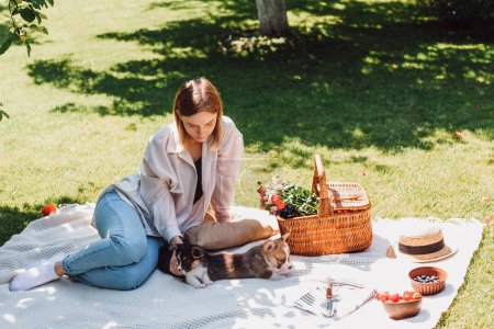 Photo for Blonde girl sitting on blanket in garden and having picnic with puppies at sunny day - Royalty Free Image