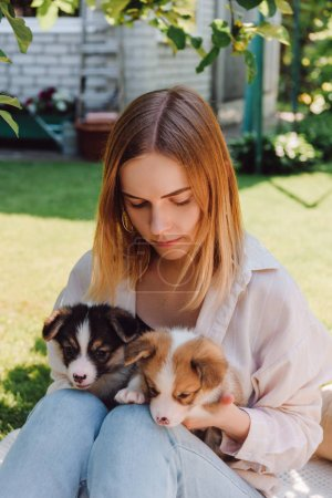 Photo for Blonde girl in garden with adorable puppies at sunny day - Royalty Free Image