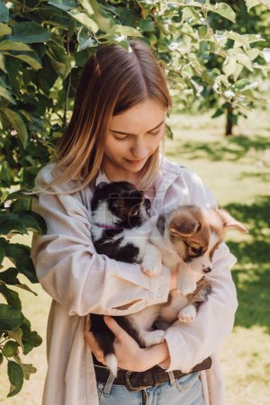 Photo for Blonde girl holding cute puppies in garden near green tree - Royalty Free Image