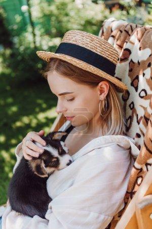 Foto de Chica rubia en sombrero de paja sosteniendo cachorro mientras se sienta en la silla de la cubierta en el jardín - Imagen libre de derechos