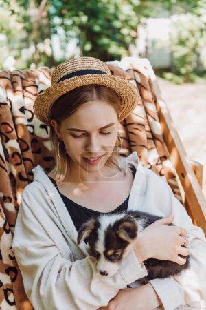 Foto de Niña rubia sonriente en sombrero de paja sosteniendo cachorro mientras se sienta en la silla de la cubierta en el jardín - Imagen libre de derechos
