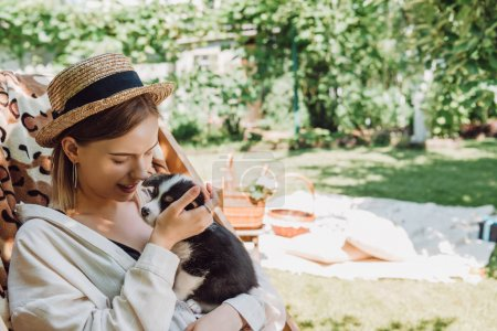 Photo for Happy blonde girl in straw hat holding puppy while sitting in deck chair in green garden - Royalty Free Image
