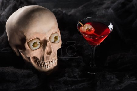 Photo for Red cocktail near spooky skull on black background - Royalty Free Image
