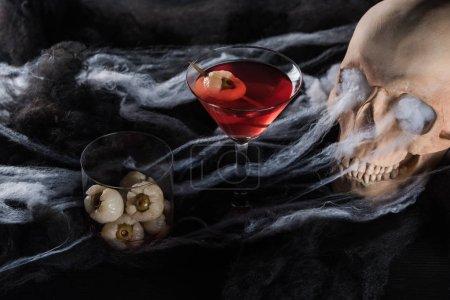 Photo pour Crâne humain effrayant dans l'éclairage rouge, décoration d'Halloween - image libre de droit