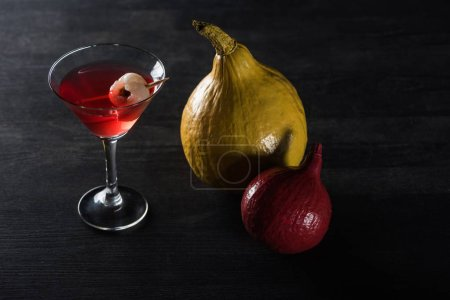 Photo for Ripe pumpkins and red cocktail on black background - Royalty Free Image