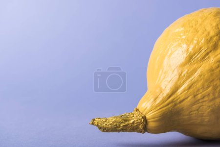 Photo for Yellow colorful painted pumpkin on violet background - Royalty Free Image