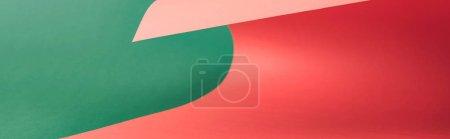 Photo pour Coup panoramique de papier rouge coloré sur le fond vert - image libre de droit