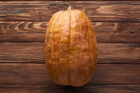 Photo for Top view of long ripe pumpkin on brown wooden surface - Royalty Free Image