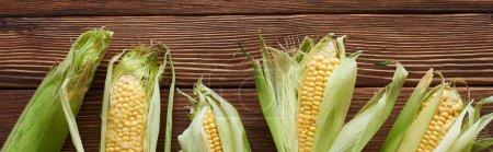 Photo pour Plan panoramique de maïs frais sur une surface en bois brun - image libre de droit