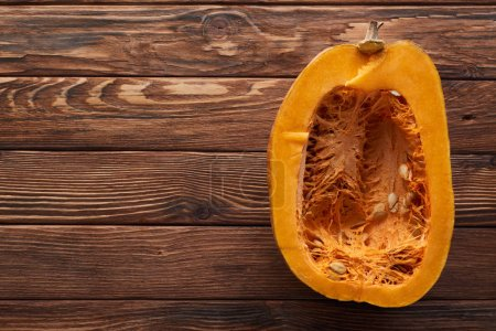 Photo for Top view of ripe pumpkin half on brown wooden surface - Royalty Free Image