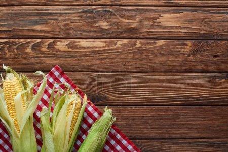 Photo pour Vue du dessus du maïs cru sur la nappe à carreaux sur la surface en bois - image libre de droit