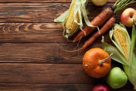 Foto de Vista superior de manzanas frescas maduras, zanahorias, calabaza y maíz dulce en la superficie de madera marrón con espacio de copia - Imagen libre de derechos