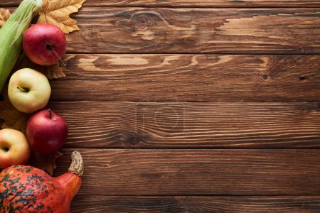Photo for Top view of pumpkin, corn and apples on brown wooden surface with dried autumn leaves - Royalty Free Image