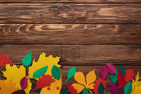 Photo for Top view of colorful paper leaves on brown wooden surface - Royalty Free Image