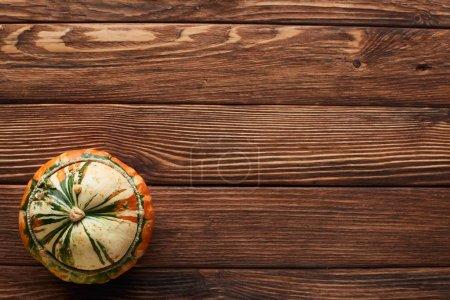 Photo pour Vue supérieure de la petite citrouille mûre sur la surface en bois brune avec l'espace de copie - image libre de droit