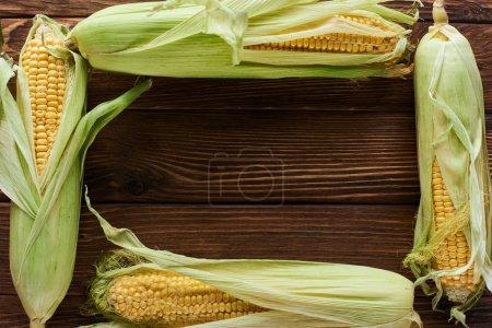 Ansicht des Rahmens von frischem Mais auf brauner Holzoberfläche