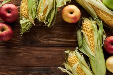 Photo for Top view of fresh apples and sweet corn on brown wooden surface with copy space - Royalty Free Image
