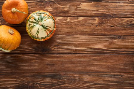Photo for Top view of fresh pumpkins on brown wooden surface with copy space - Royalty Free Image