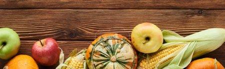 Photo pour Coup panoramique de pommes fraîches, de citrouilles et de maïs sucré sur une surface en bois - image libre de droit
