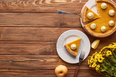 Photo for Cut pumpkin pie with whipped cream, apple, and yellow flowers on wooden surface - Royalty Free Image