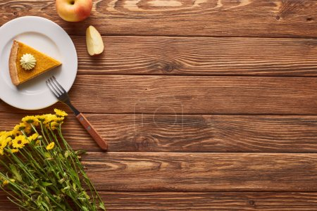 Photo for Piece of pumpkin pie with whipped cream near fork, apple, and yellow flowers on wooden surface - Royalty Free Image