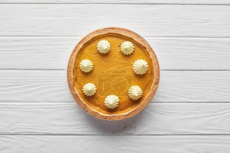 Photo for Top view of delicious pumpkin pie with whipped cream on white wooden surface - Royalty Free Image