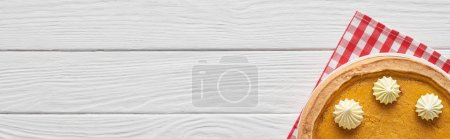 Photo for Delicious pumpkin pie with whipped cream and checkered napkin on white wooden table - Royalty Free Image