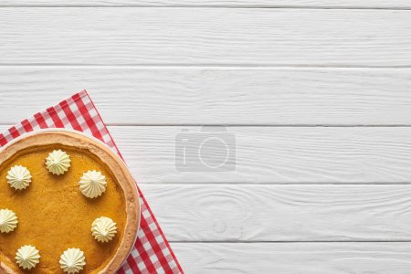 Photo for Tasty pumpkin pie with whipped cream on checkered napkin on white wooden surface - Royalty Free Image