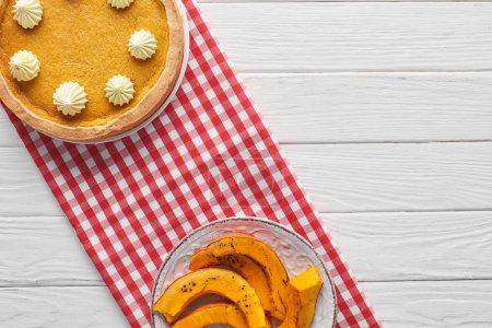Photo pour Délicieuse tarte à la citrouille avec crème fouettée sur une serviette à carreaux près de la citrouille tranchée cuite au four sur une table en bois blanc - image libre de droit