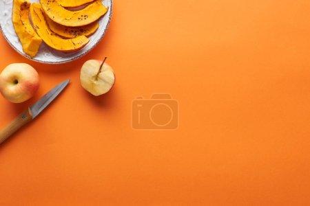 Photo pour Tranches de citrouille cuite au four près de l'ensemble et couper les pommes et le couteau sur la surface orange avec espace de copie - image libre de droit