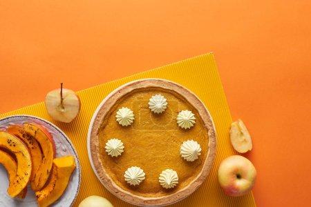 Photo pour Tarte à la pumkin savoureuse avec crème fouettée près de la citrouille cuite au four, pommes entières et coupées sur la surface orange - image libre de droit
