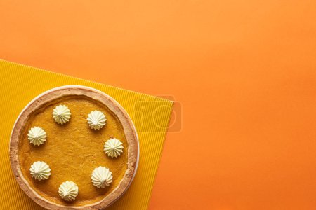 top view of delicious pumpkin pie with whipped cream and textured napkin on orange surface