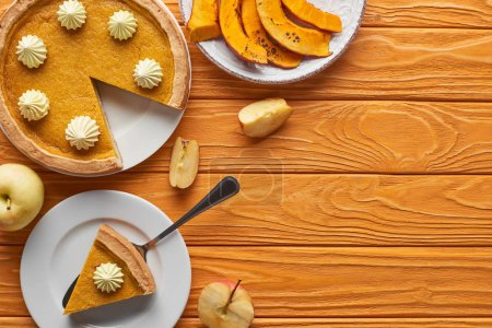 Photo for Delicious pumpkin pie with whipped cream near baked pumpkin, whole and cut apples on orange wooden table - Royalty Free Image