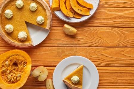 Photo for Delicious, cut pumpkin pie with whipped cream near baked and raw pumpkins, and cut apple on orange wooden table - Royalty Free Image