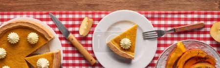 Photo for Panoramic shot of pumpkin pie with whipped cream on checkered tablecloth near baked pumpkin, fork, knife, and cut apples on brown wooden table - Royalty Free Image