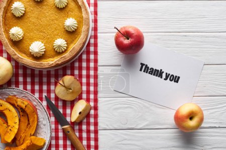 Photo for Top view of pumpkin pie, ripe apples and thank you card on wooden white table - Royalty Free Image