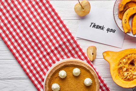 top view of pumpkin pie, ripe apples and thank you card on wooden white table with plaid napkin