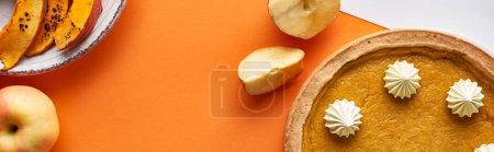 Photo pour Vue du dessus de tarte à la citrouille, pommes mûres sur fond orange, vue panoramique - image libre de droit