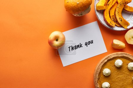 Photo for Top view of pumpkin pie, ripe apples and thank you card on orange background - Royalty Free Image