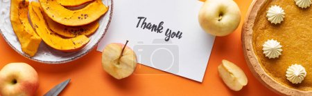Photo for Top view of pumpkin pie, ripe apples and thank you card on orange background, panoramic shot - Royalty Free Image