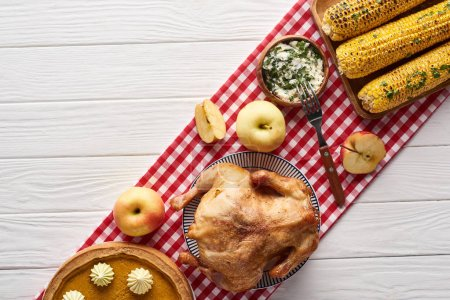 Photo for Top view of pumpkin pie, turkey and vegetables served at white wooden table on red plaid napkin for Thanksgiving dinner - Royalty Free Image