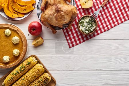 Photo for Top view of pumpkin pie, turkey and vegetables served at white wooden table for Thanksgiving dinner - Royalty Free Image