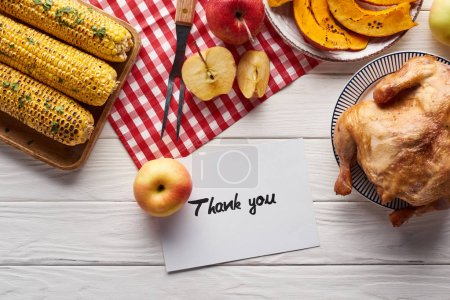 top view of pumpkin pie, turkey and vegetables served at white wooden table with thank you card for Thanksgiving dinner