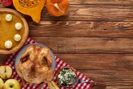 Photo for Top view of pumpkin pie, turkey and vegetables served at wooden table for Thanksgiving dinner - Royalty Free Image