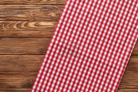 Photo for Top view of red checkered napkin on wooden brown table - Royalty Free Image