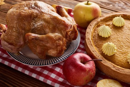 pumpkin pie, roasted turkey and apples on red checkered napkin at wooden table for Thanksgiving dinner