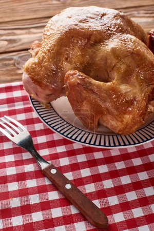 Photo for Roasted turkey and fork served on red checkered napkin at wooden table for Thanksgiving dinner - Royalty Free Image