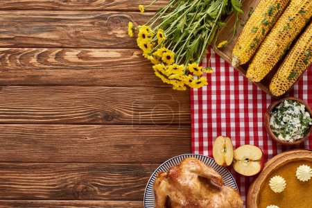 Photo for Top view of pumpkin pie, roasted turkey and corn served at wooden table near yellow flowers for Thanksgiving dinner - Royalty Free Image