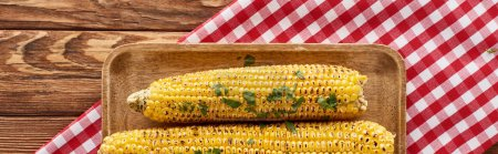 Photo for Top view of grilled corn served on red checkered napkin at wooden table for Thanksgiving dinner, panoramic shot - Royalty Free Image